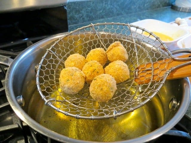 Fried Bocconcini Balls going into a pot of oil