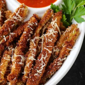 Fried eggplant strips in a white bowl with sauce
