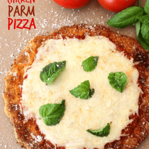 Chicken Parm Pizza on a pizza stone with tomatoes and fresh basil