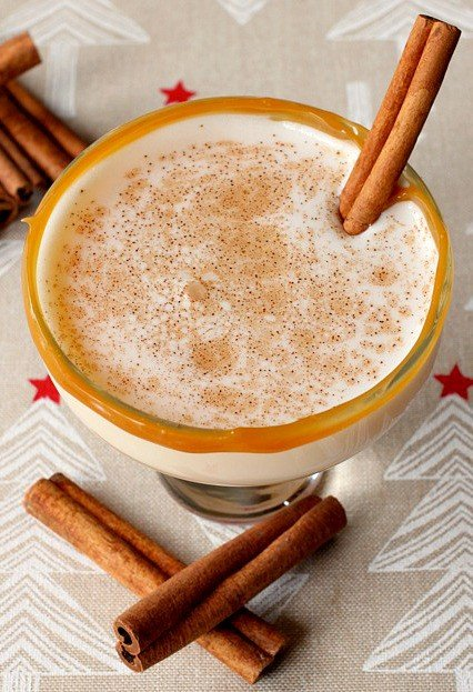 An Eggnog Cocktail is made with eggnog, amaretto and vodka, then rimmed with caramel and garnished with cinnamon.