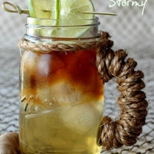 A Dark and Stormy cocktail in a mason jar cup with limes