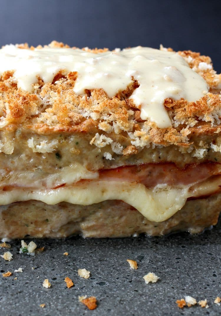 A chicken meatloaf with layers of ham and cheese and a dijon cream sauce