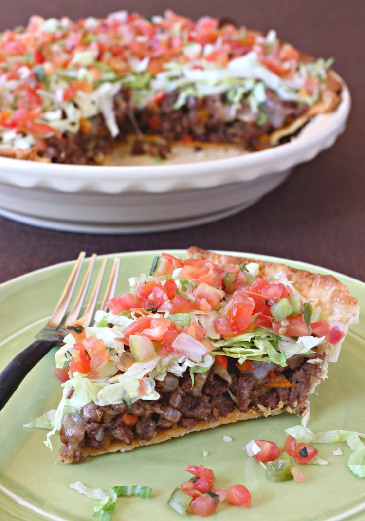 A slice of taco pie loaded with lettuce, tomatoes, meat and cheese on a green plate