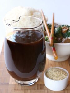 A big glass pitcher filled with homemade Stir Fry Sauce next to a bowl of sesame seeds
