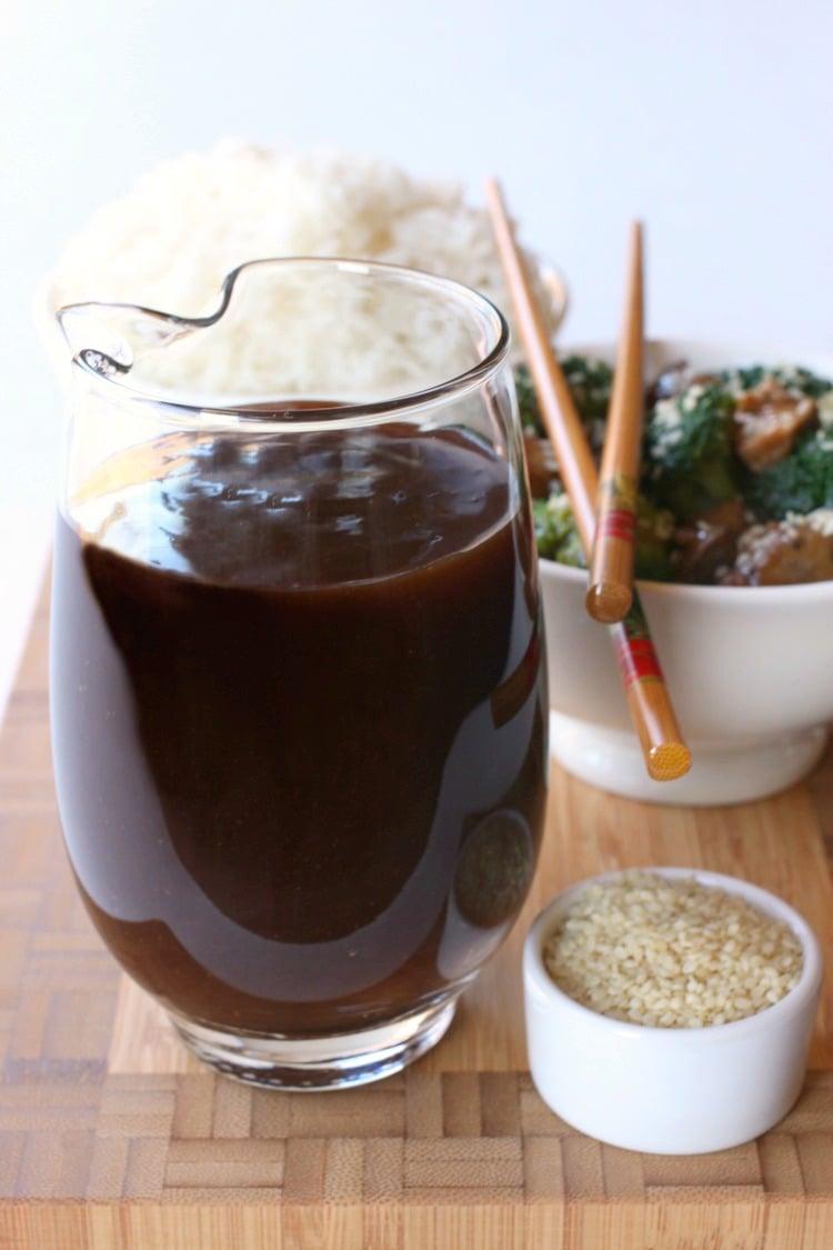 A big glass pitcher filled with homemade Stir Fry Sauce next to a bowl of sesame seeds