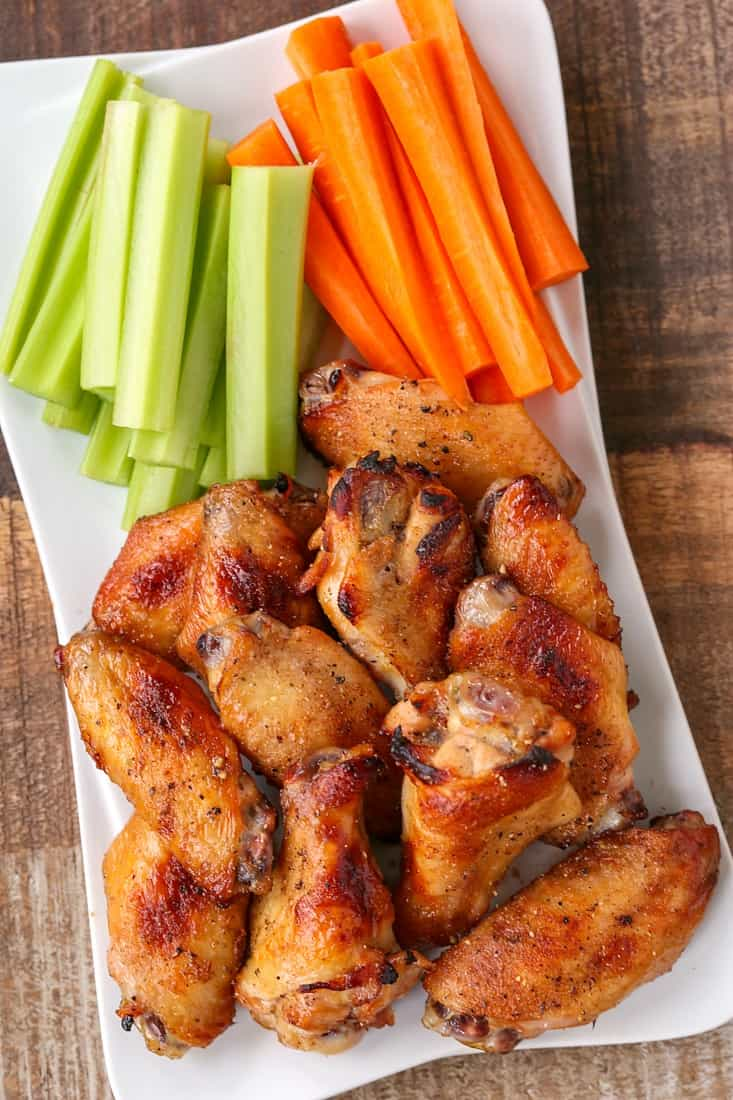 Baked chicken wings with carrots and celery on a platter