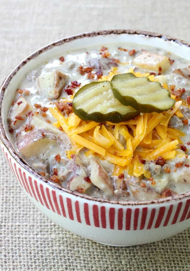 cheeseburger chowder recipe in a bowl with pickles