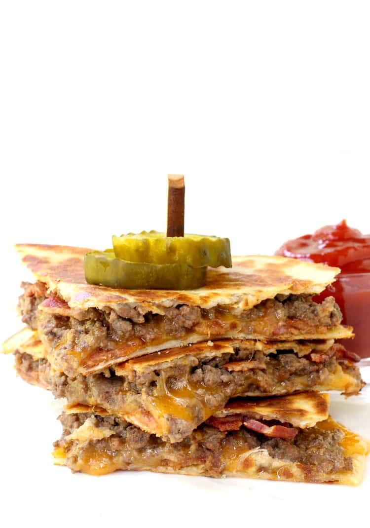 Bacon Cheeseburger Quesadillas stacked on a white plate with pickles