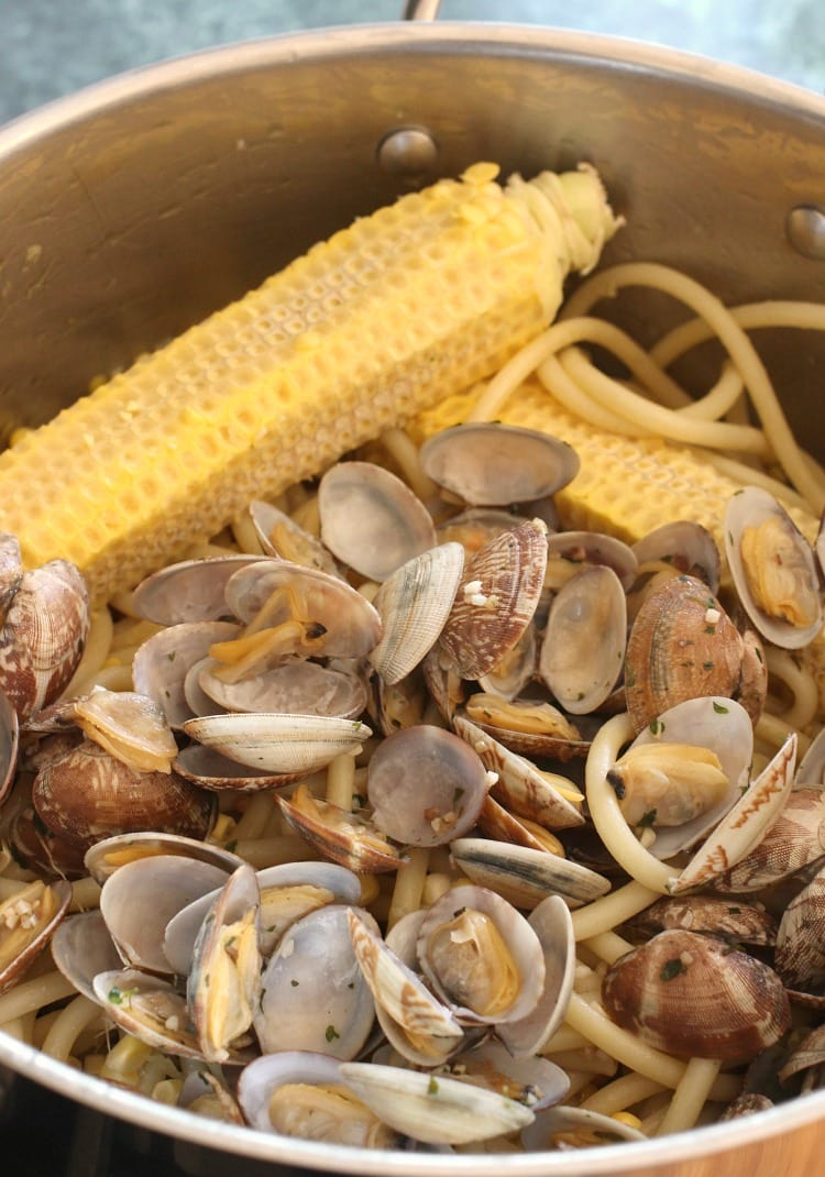 corn on the cob in a pot with clams