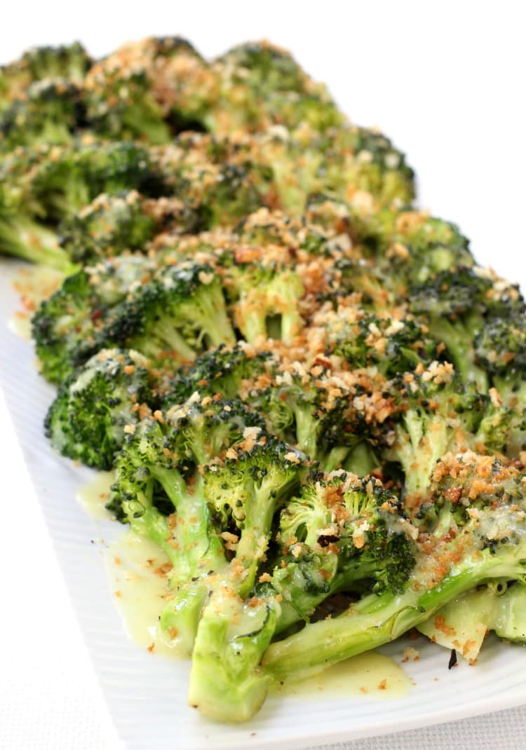 Roasted broccoli on a serving platter with toasted breadcrumbs and sauce