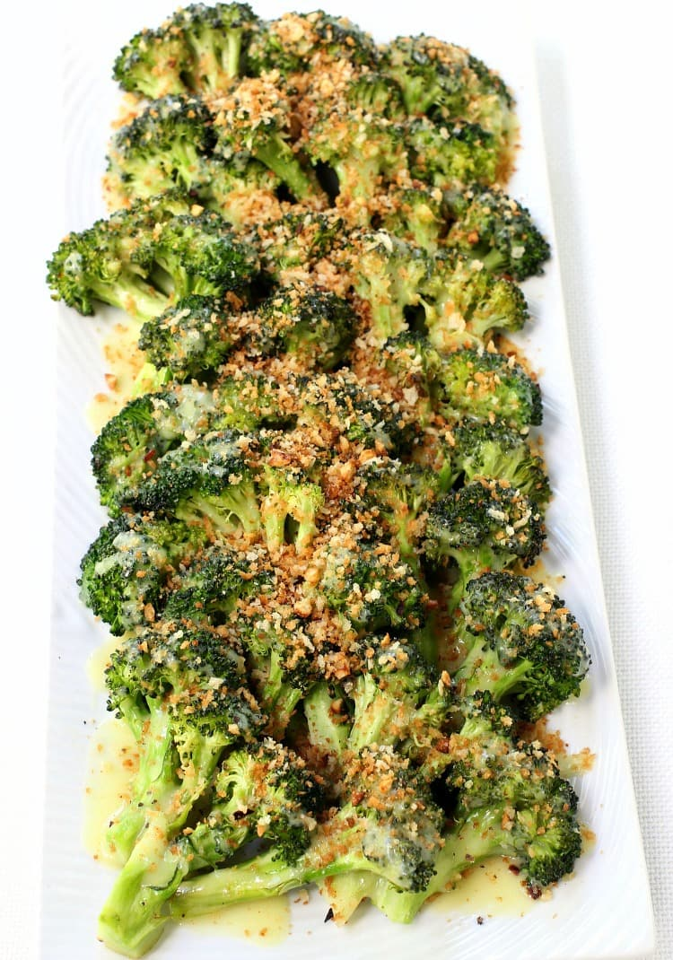 Roasted broccoli on a platter with breadcrumbs and hollandaise sauce
