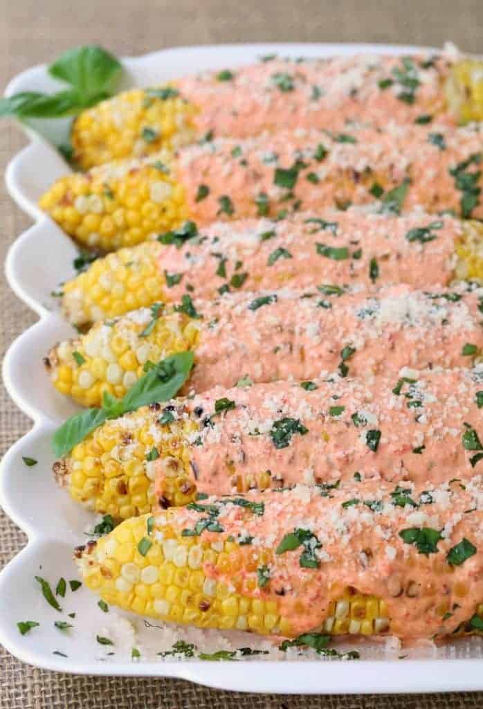 Grilled Corn on the cob topped with red pepper mayo, cheese and basil!