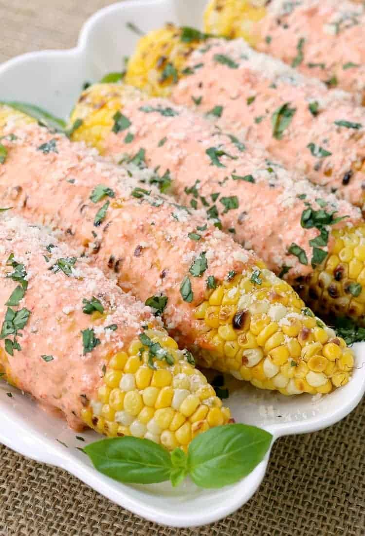 Grilled Italian Street Corn covered with red pepper mayo and cheese!