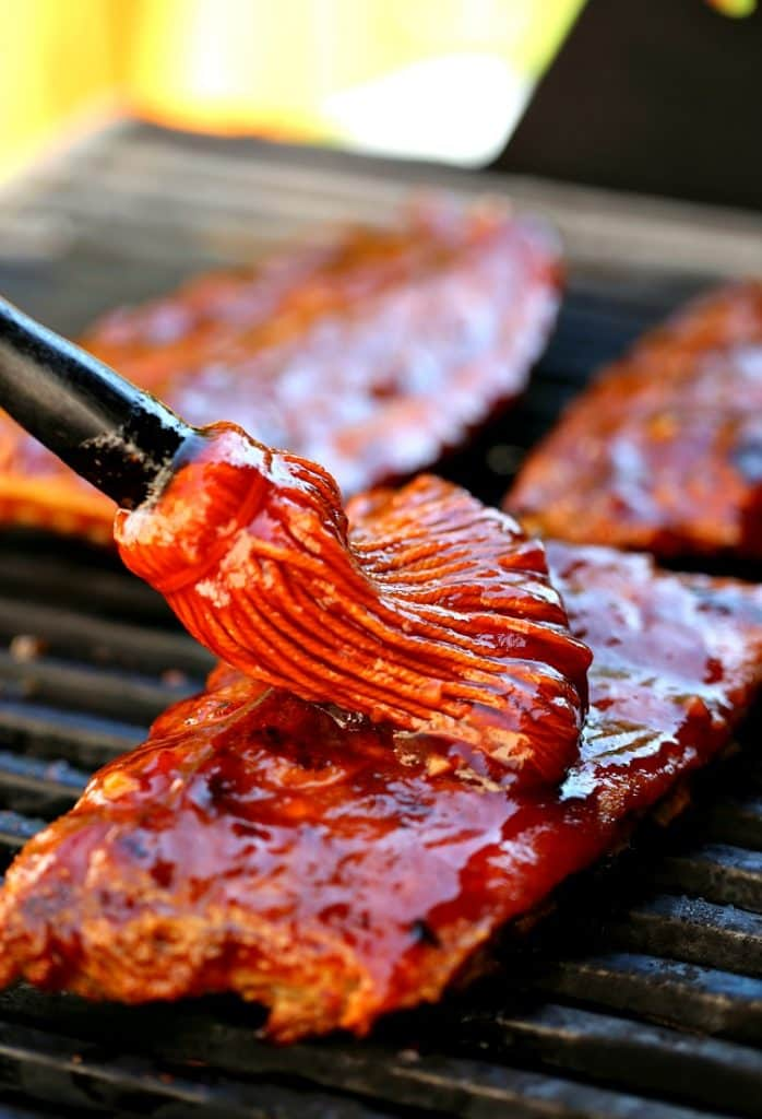 Sticky Root Beer BBQ Ribs on the grill with sauce.