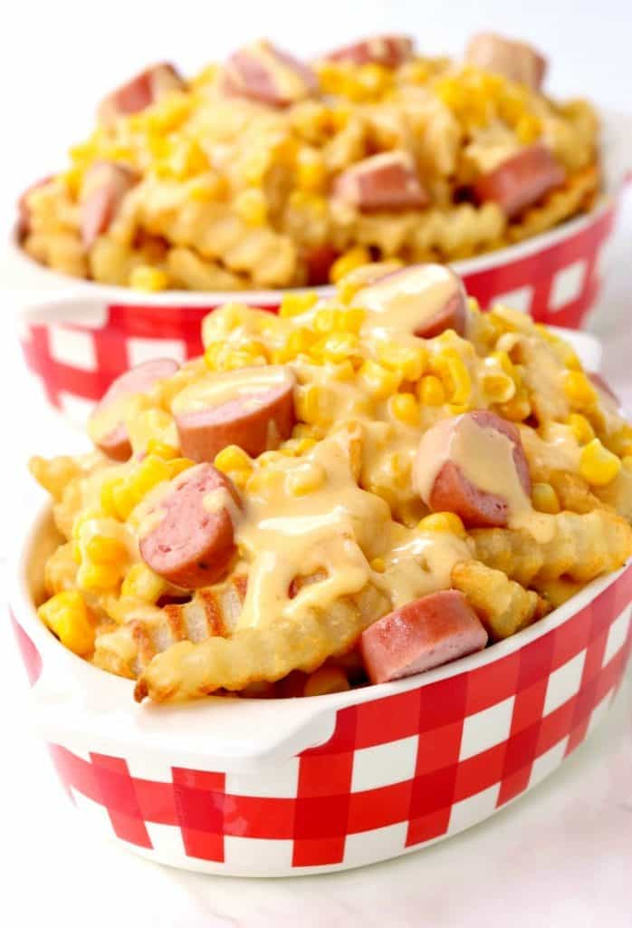 This Corn Dog Poutine is topped with cheese sauce, corn and hot dogs!