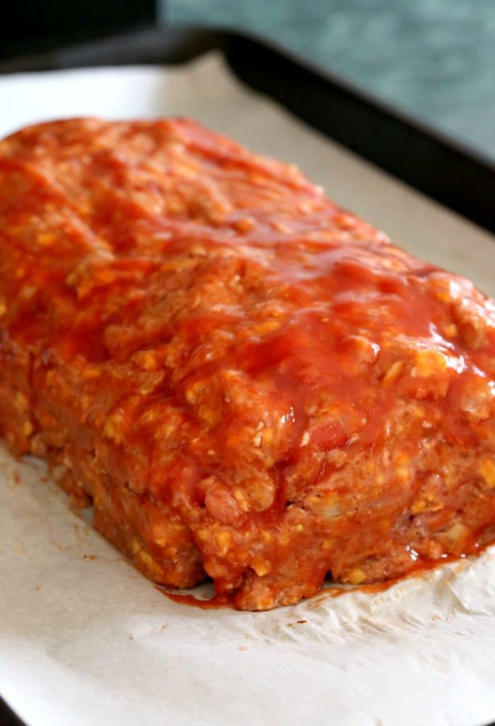 Turkey Taco Meatloaf with sauce on a baking sheet