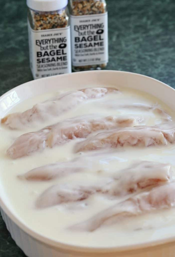 Chicken Tenders soaking in buttermilk for a chicken finger recipe
