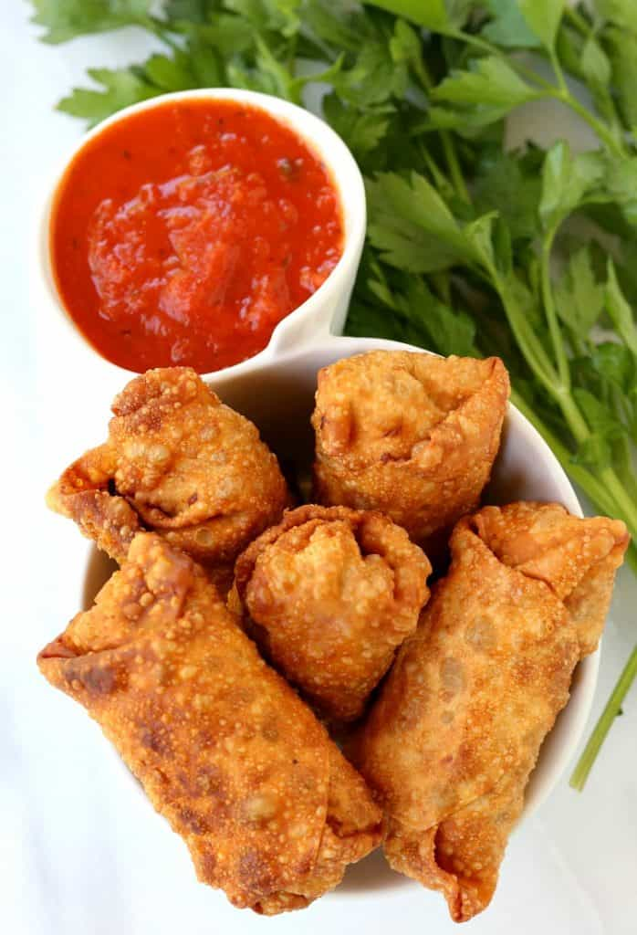 Italian Egg Rolls in a bowl with marinara dipping sauce