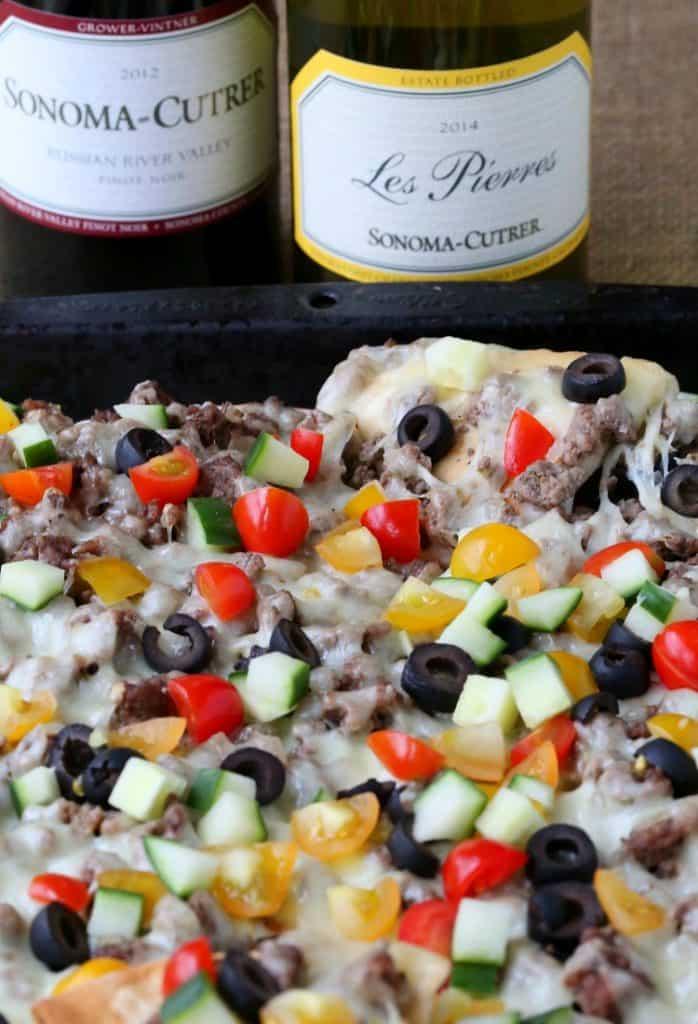 greek nachos on a baking sheet with wine bottle