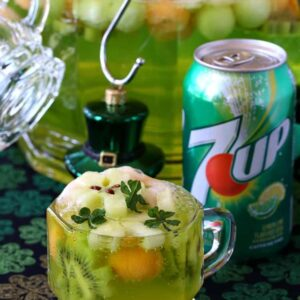 Punch glass filled with punch next to 7UP can and punch bowl