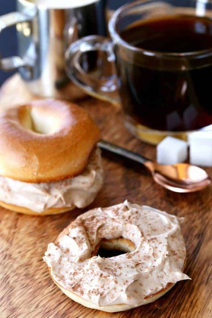 Spreading coffee flavored cream cheese on a bagel
