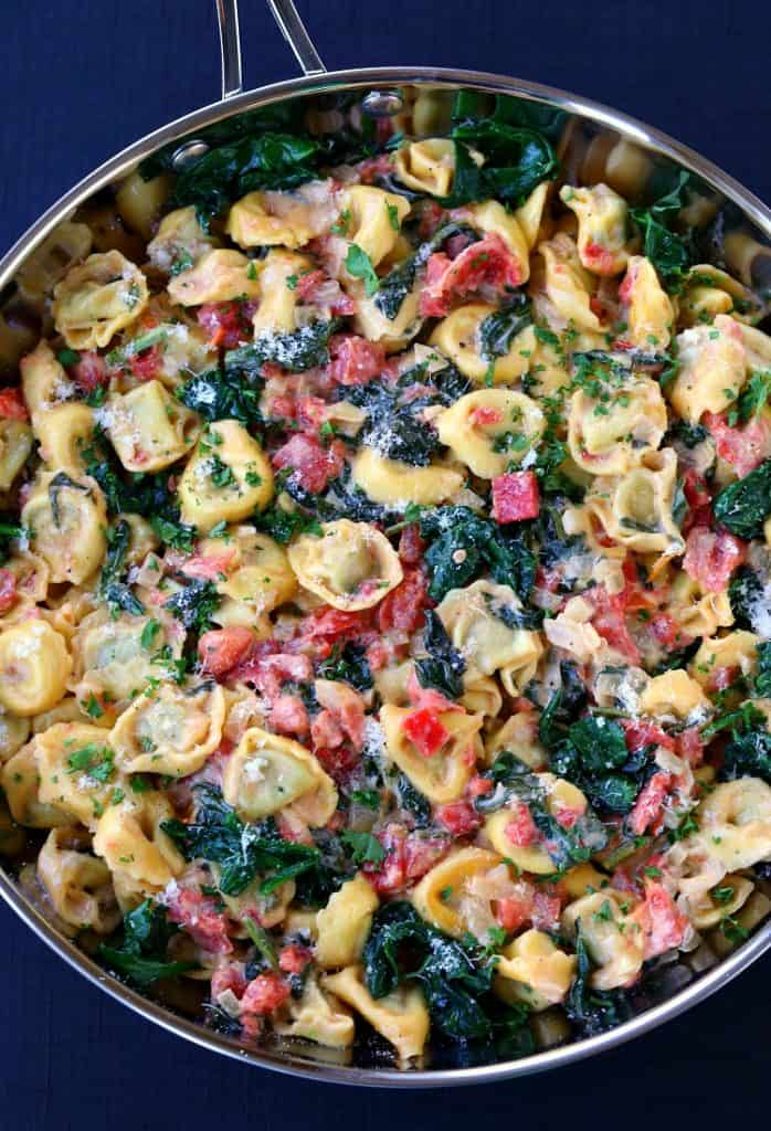 tortellini with spinach and tomatoes in skillet