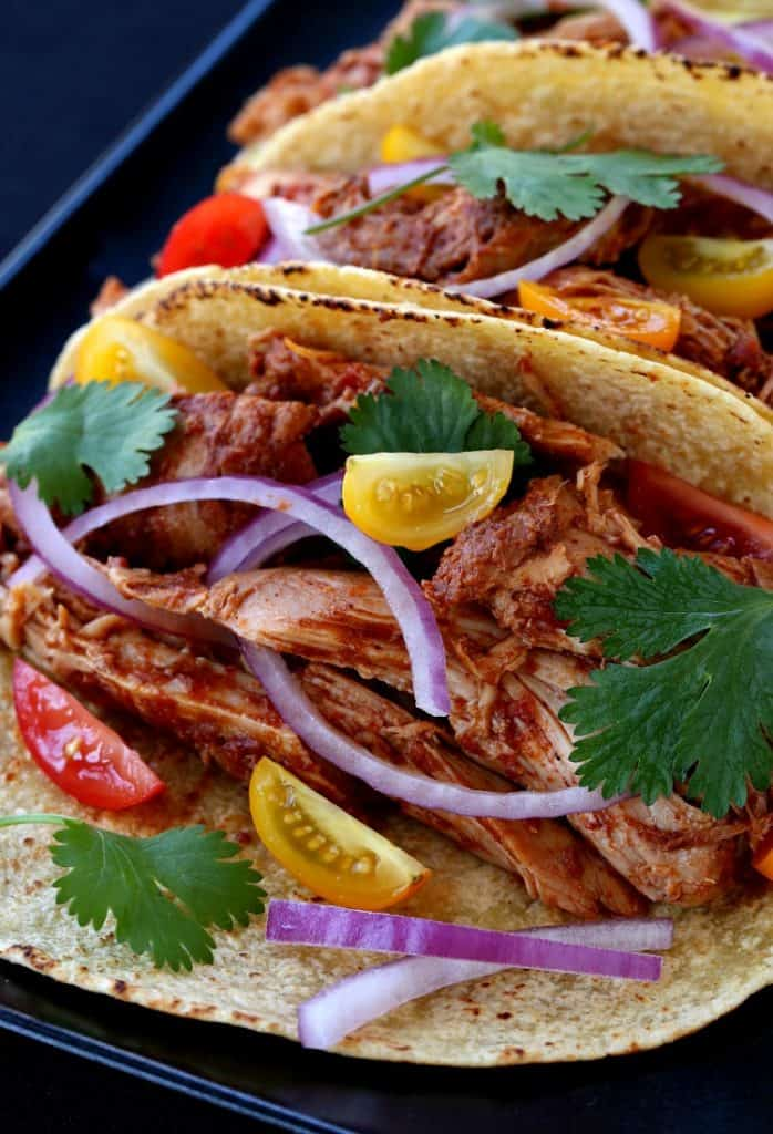 Slow cooker turkey mole tacos with onions and tomatoes on a tray