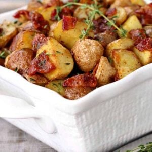 Crispy Oven Roasted Bacon Potatoes in a white dish with thyme