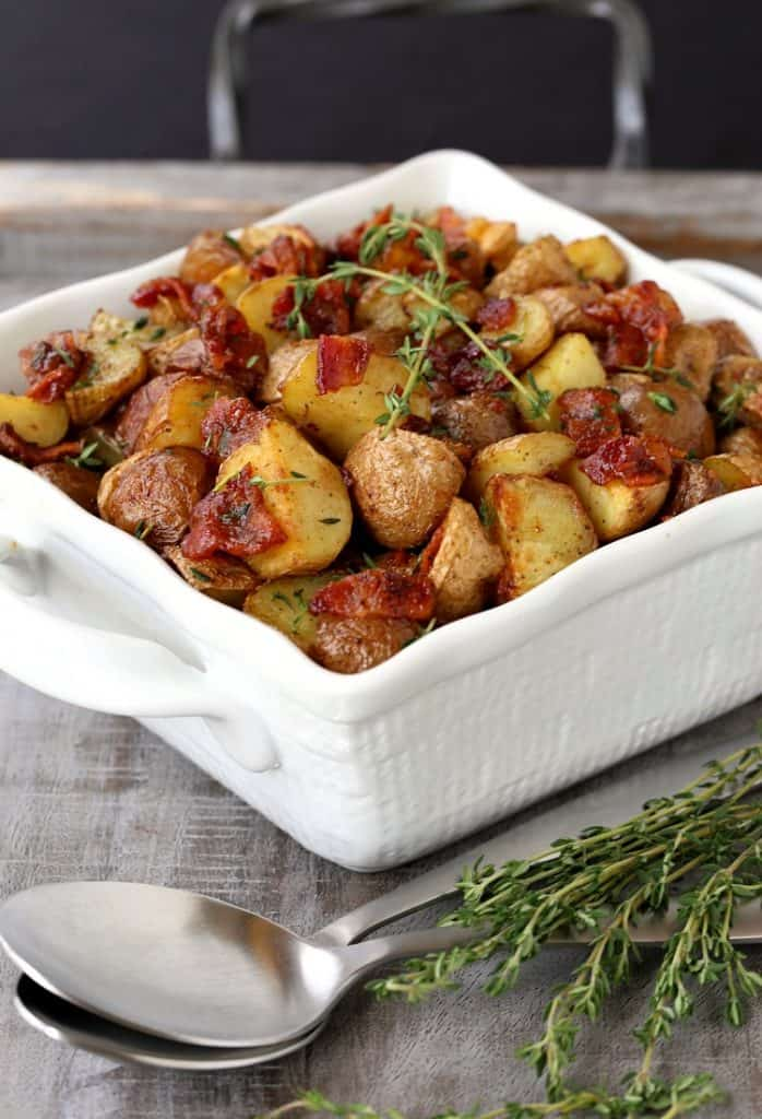 Crispy Oven Roasted Bacon Potatoes in a white bowl on a board