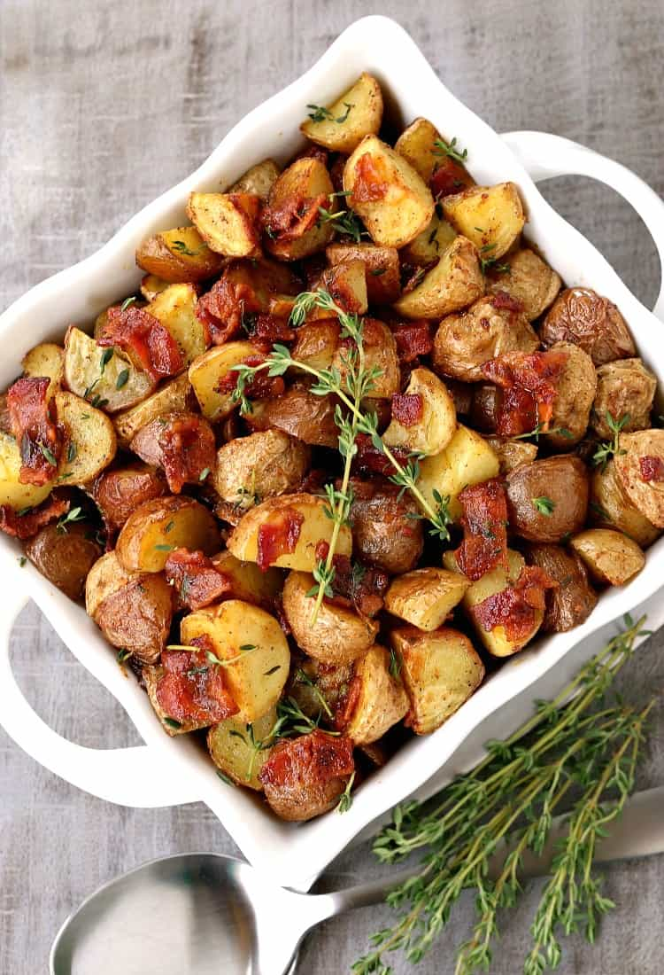 Crispy Oven Roasted Bacon Potatoes in a white bowl from the top view with spoons