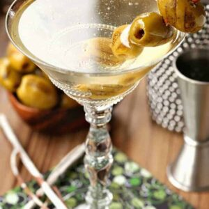 Grilled Dirty Martini in glass with shaker and olives