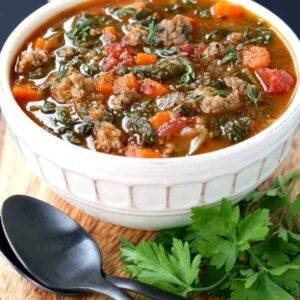 Low Carb Sausage Vegetable Soup in a bowl on a board with spoons