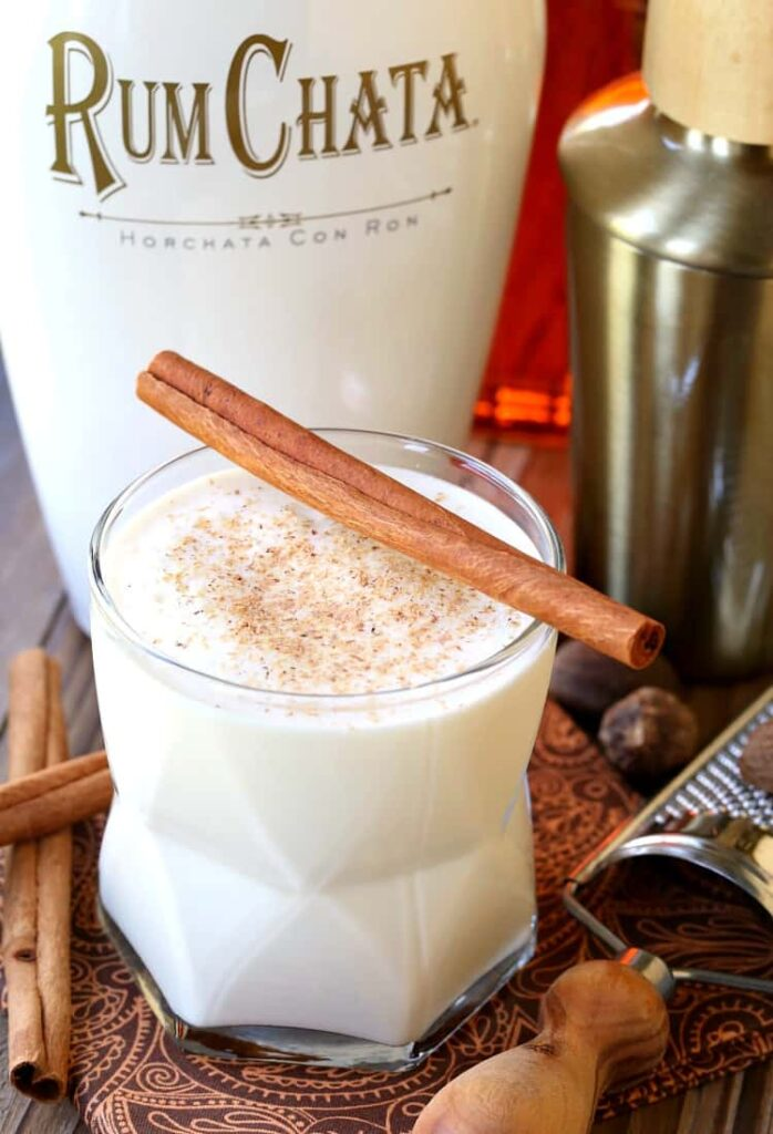 Campfire Milk Punch in a glass with a bottle of RumChata