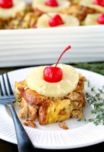 Upside Down Pineapple Sausage Stuffing on a plate with a baking dish behind it