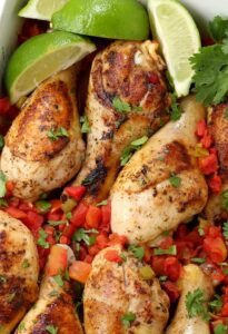 Oven Baked Fiesta Chicken Legs in a dish with limes