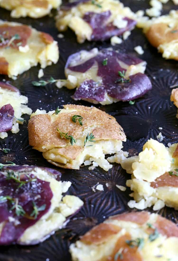 smashed potatoes with thyme on a sheet pan