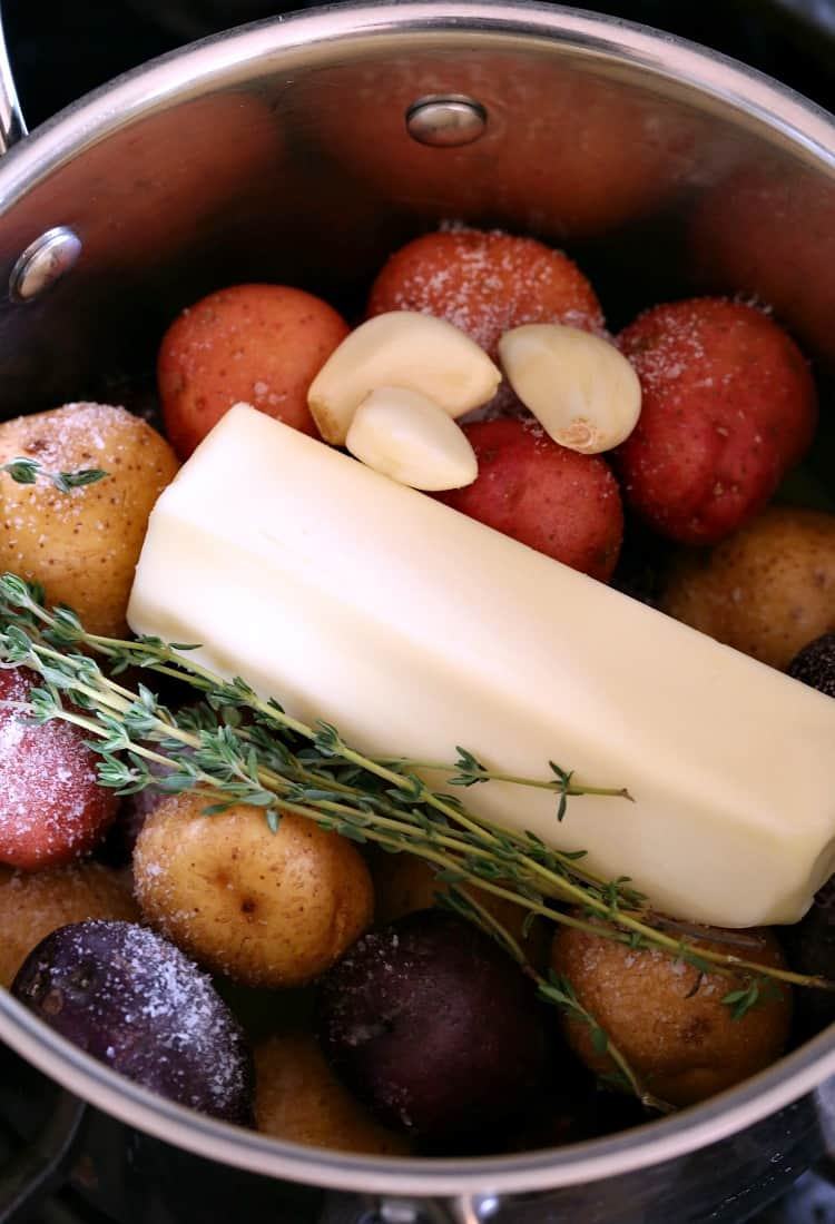 stick of butter in a pot with potatoes