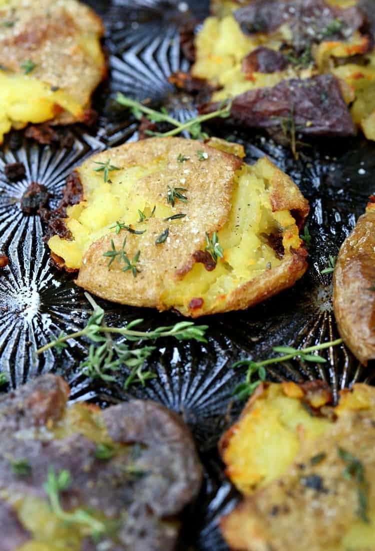 smashed potatoes on a black sheet pan