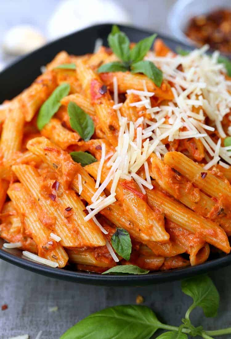 Easiest Penne Vodka Ever in a bowl with cheese and basil