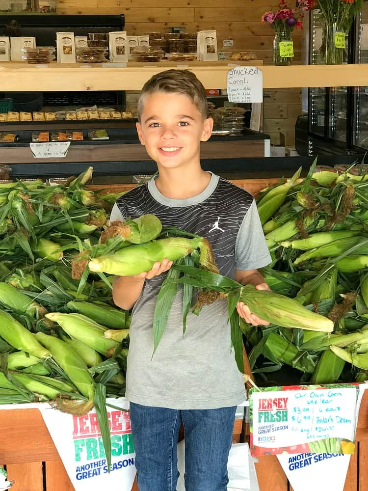 Evan at the farm stand with corn