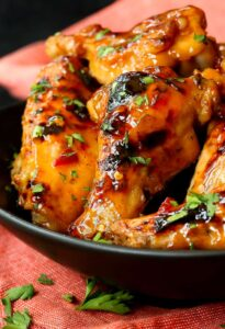 Slow Cooker Sweet Chili Chicken Wings close up in a black dish with a red towel