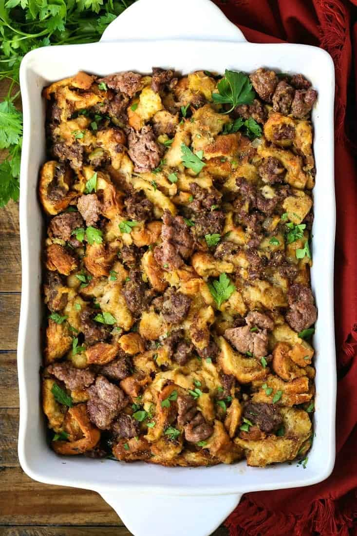 the best sausage stuffing in a baking dish on a wood board