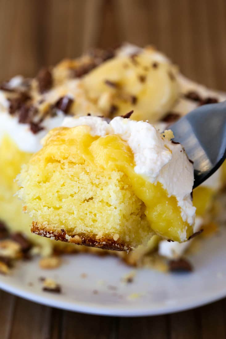 Banana Bourbon Poke Cake is an easy party cake recipe with whipped cream, pudding and bananas