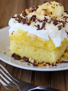 Banana Bourbon Poke Cake is an easy dessert recipe with layers of whipped cream and banana pudding