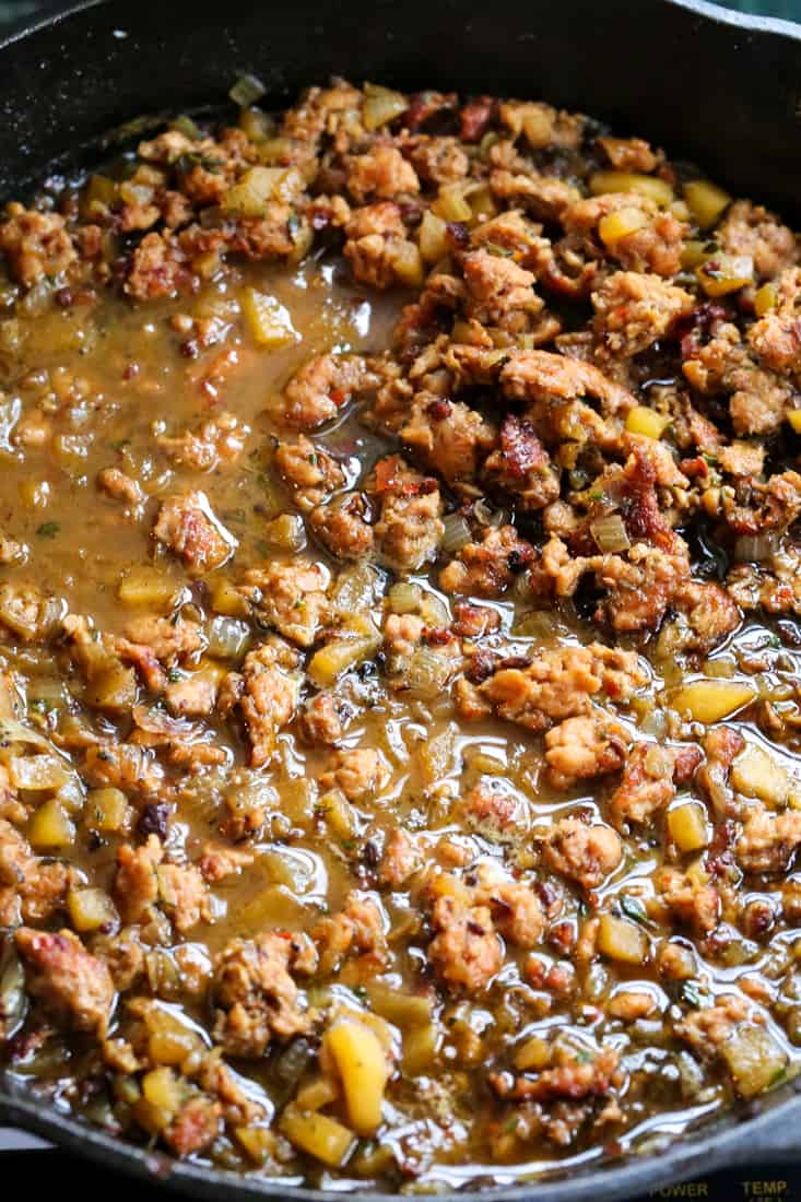 Spicy Sausage Cornbread Dressing is a make ahead side dish that starts by simmering sausage and apples in chicken broth