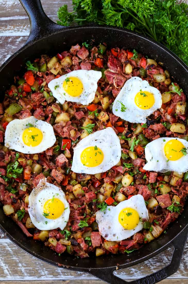 Corned Beef Hash in a skillet with fried eggs on top