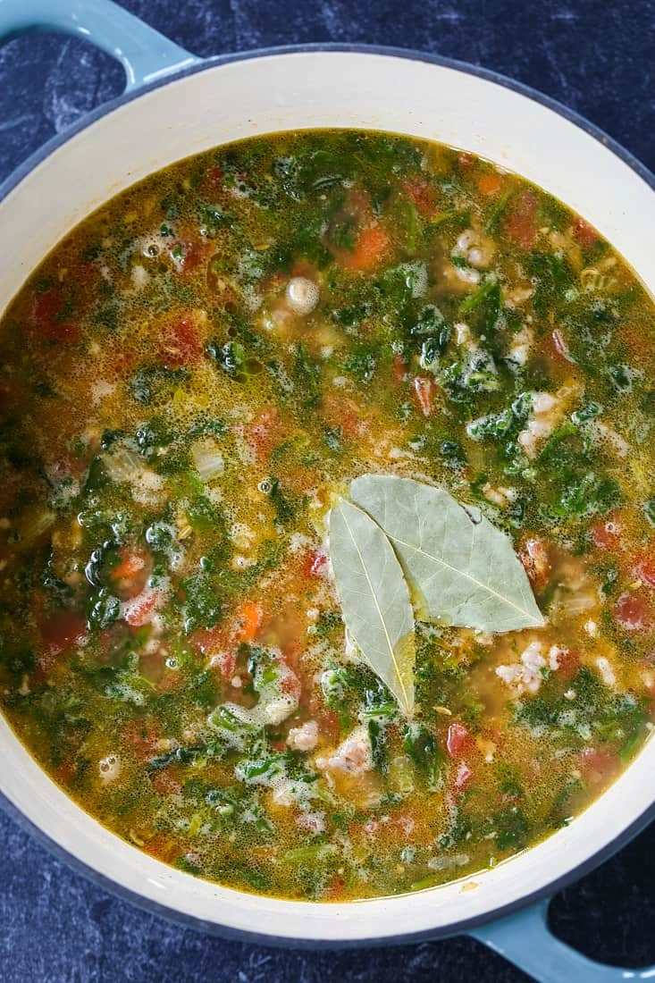 sausage and farro soup with spinach simmering in pot