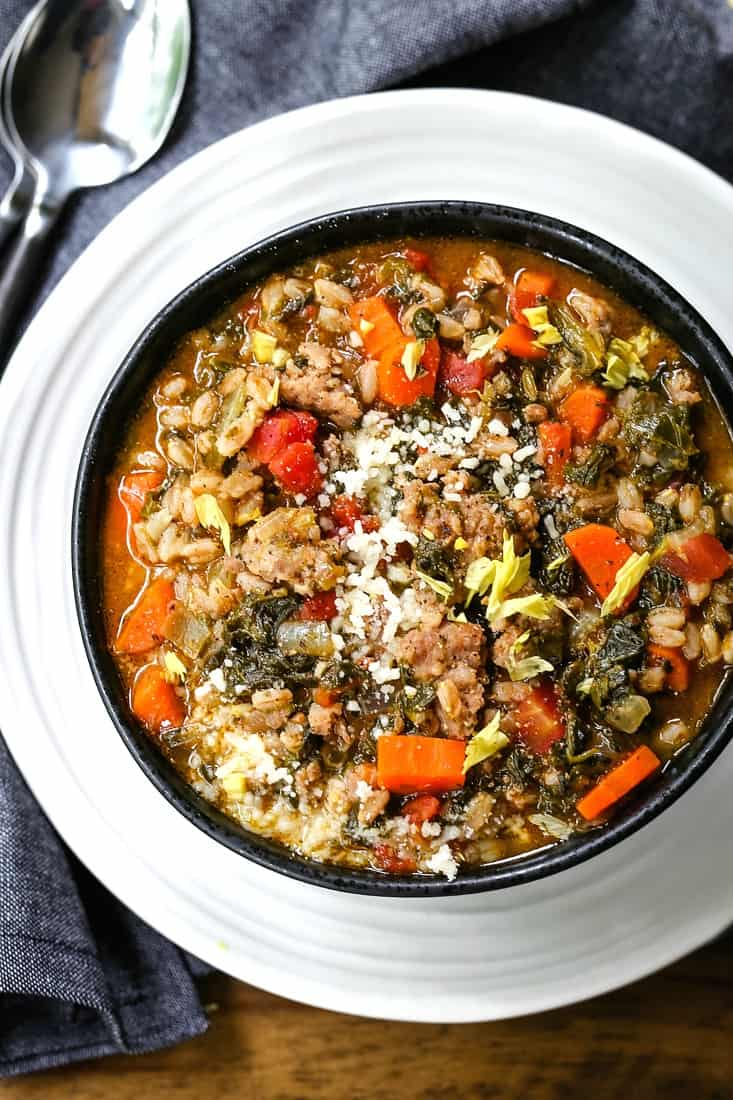 bowl of sausage soup with spinach and farro