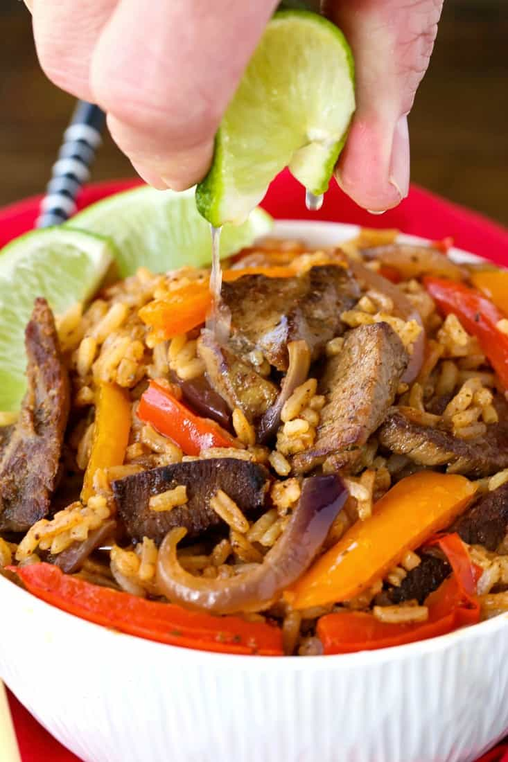 Steak Fajita Fried Rice in a bowl with a lime squeeze