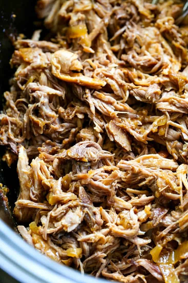 Slow Cooker Pulled Pork is shredded and mixed with the cooking liquid and onions
